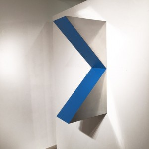 """Arno Kortschot –""""Inward Triangle"""" 39 x 10 x 19 inches zinc, panel , acrylic paint. This composition, with it's pointed edges and strong geometric form next to a painting with horizontal lines, or circles or other geometric elements, that are not the main composition, enhance each other. Vertical next to horizontal is a great contrast."""