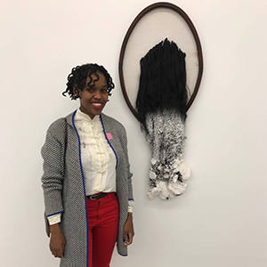 Sethembile Msezane stands before her sculpture entitled Kwasuka Sukela, © 2016. 66 x 47 cm. Cloth, hair, salt, and wood. Photo by author, Sept. 16, 2017.