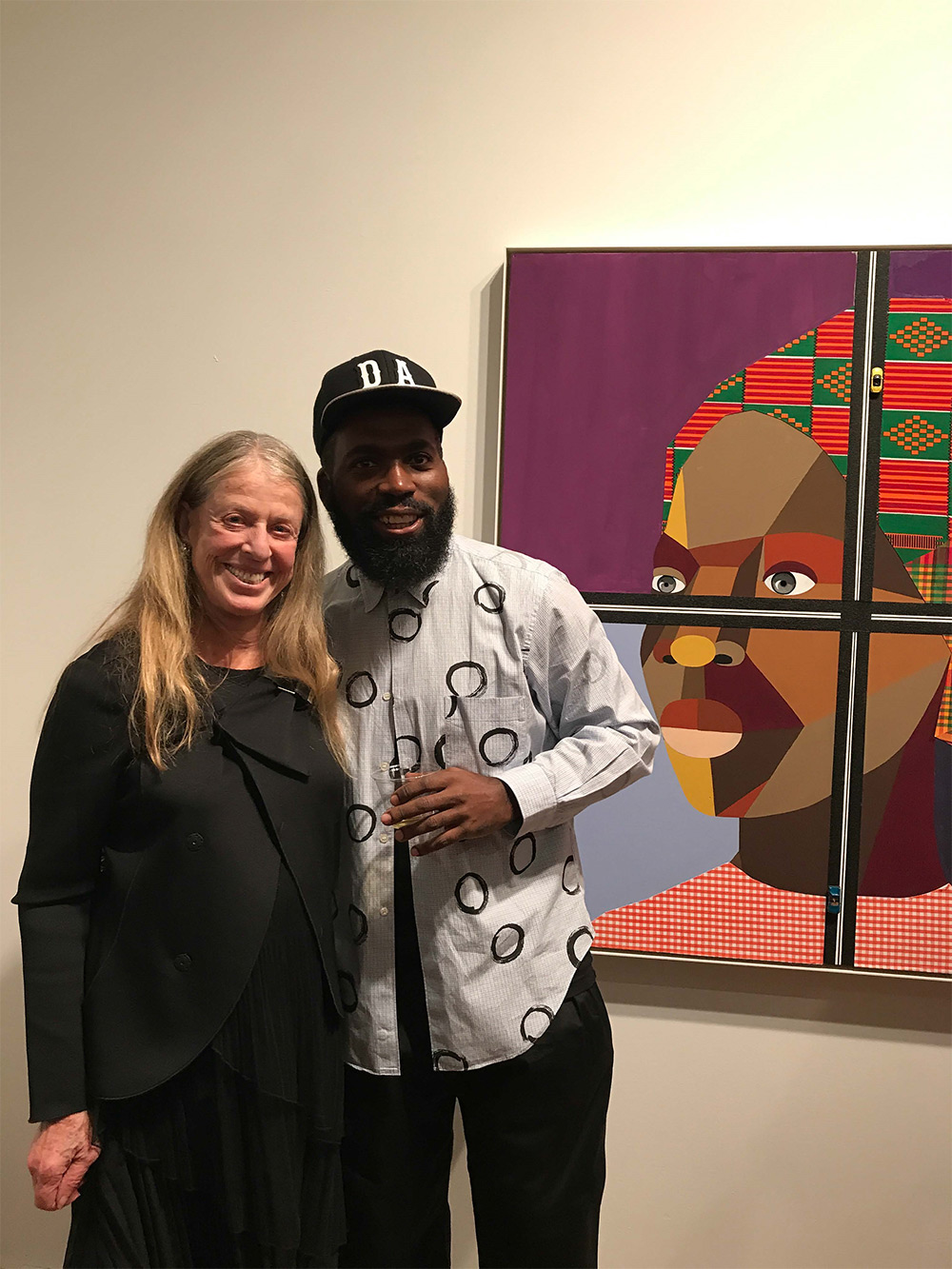 "Barbara Hoffman with Derrick Adams at his opening for Figures in the Urban Landscape, Nov. 8, 2017. In the background: ""Figure in the Urban Landscape 3,"" 2017, by Derrick Adams. Tilton Gallery, courtesy of author."